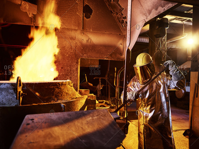 Worker holding metal rod in furnace at foundry