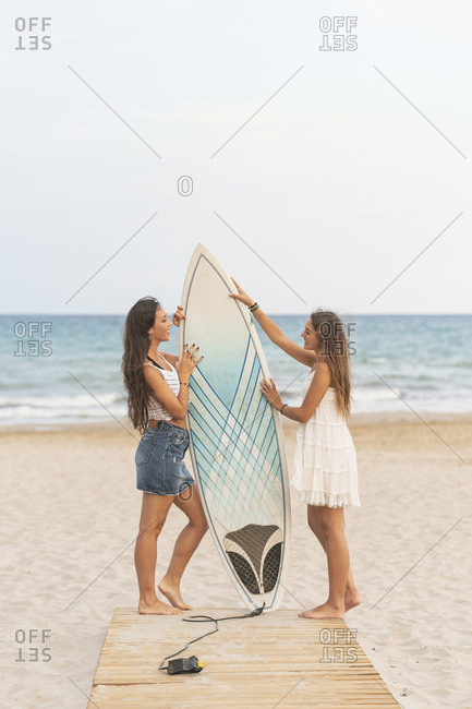 Two happy female friends with surfboard standing on boardwalk on the beach