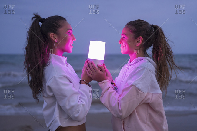 Two female friends holding led light on the beach at night