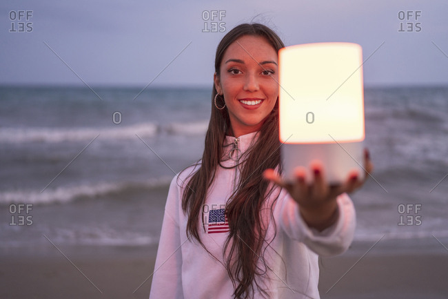 Portrait of young woman holding led light on the beach at night