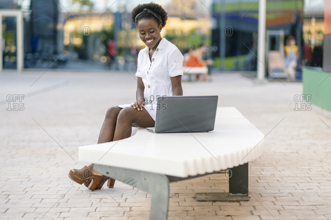 Portrait of smiling young woman sitting on bench looking at laptop