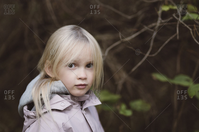 Portrait of staring little girl in the woods