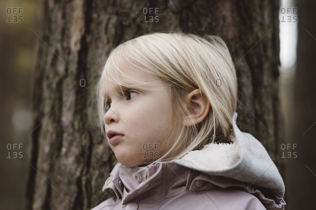 Portrait of blond little girl in front of tree trunk