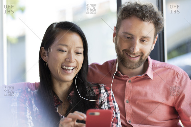Happy man and woman with cell phone and earbuds in a cafe