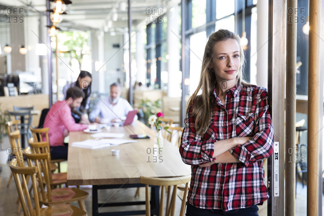 Portrait of casual businesswoman in a cafe with colleagues having a meeting in background
