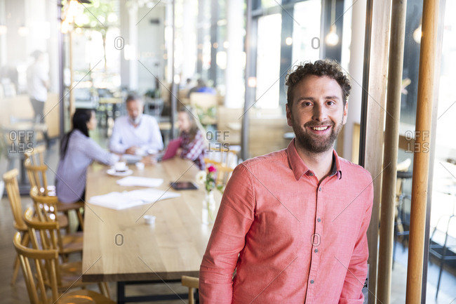 Portrait of casual businessman in a cafe with colleagues having a meeting in background