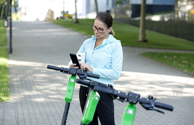 Mature woman scanning QR Code for activating rental electric scooter