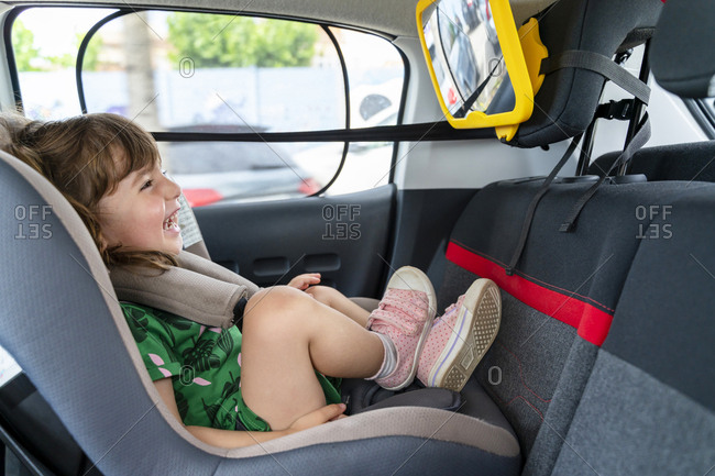 Laughing toddler girl sitting in a car seat looking in a mirror