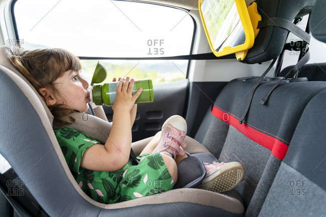 Toddler girl sitting on a car seat with a mirror drinking water