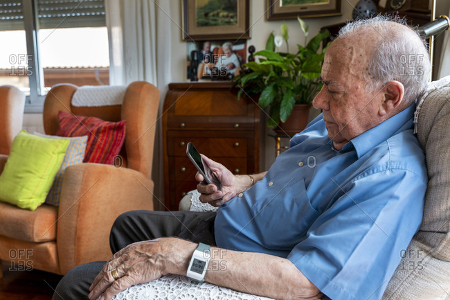 Elderly man using a mobile phone and wearing a smart emergency alarm bracelet around wrist at home