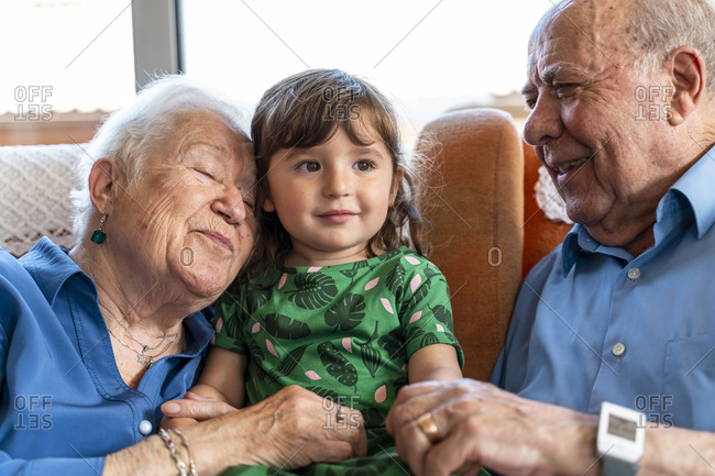 Grandparents spending time with the granddaughter in living room