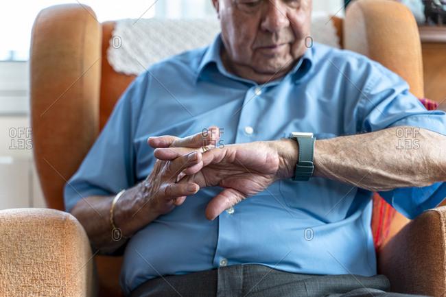 Elderly man wearing a smart emergency alarm bracelet around wrist at home