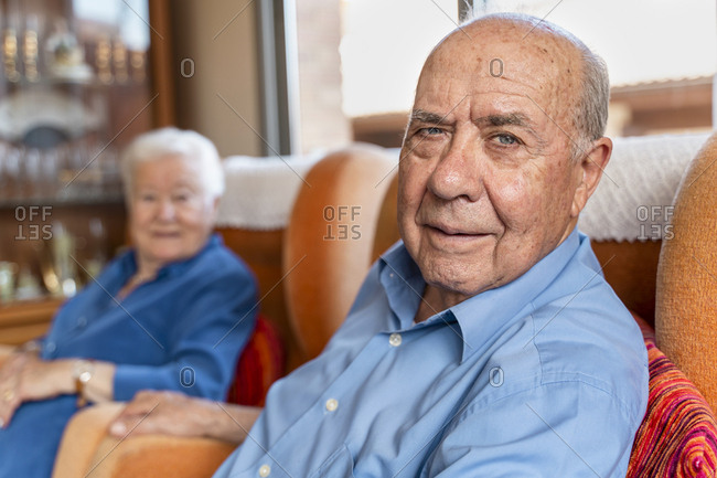 Elderly man with his wife sitting in an armchair in living room