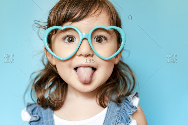 Portrait of cute little girl with tongue out and heart shaped glasses on blue background