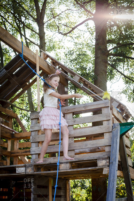 Girl dressed as a princess with crown and scepter playing in a tree house