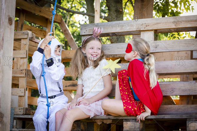 Three kids with superheroes costumes playing on their tree house