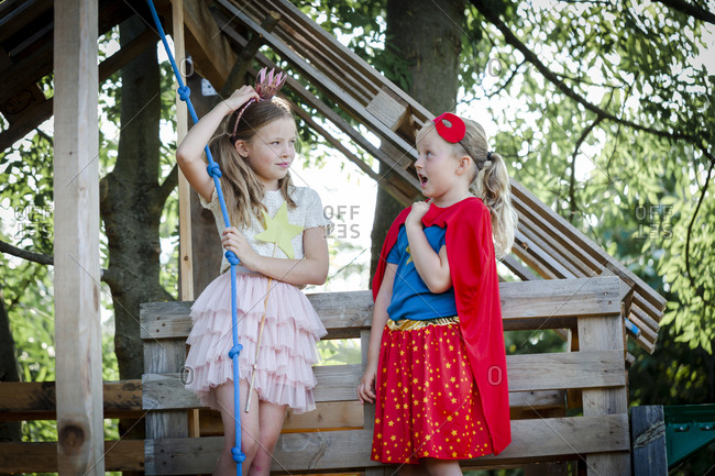 Girls dressed up as princess and superwoman playing in a tree house
