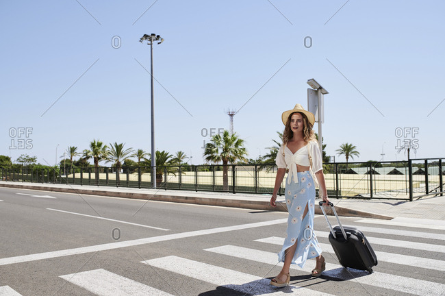 Young woman with baggage crossing a street at the airport