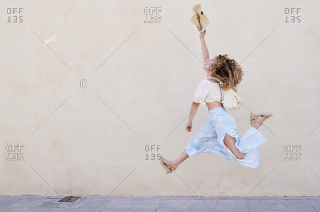 Carefree young woman with hat jumping at a wall