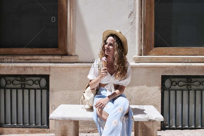 Young woman sitting on stone bench eating ice cream