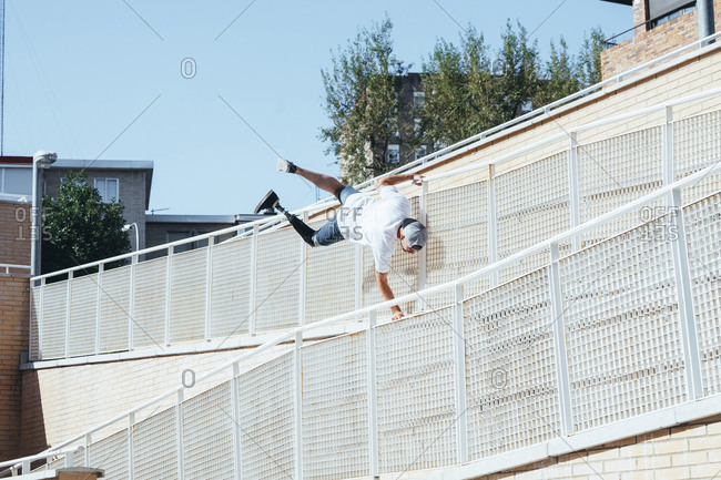 Young man with leg prosthesis performing parkour in the city