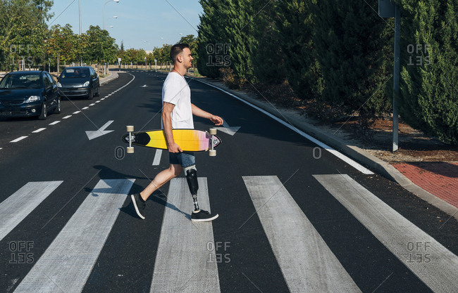 Young man with leg prosthesis holding skateboard and walking on crosswalk