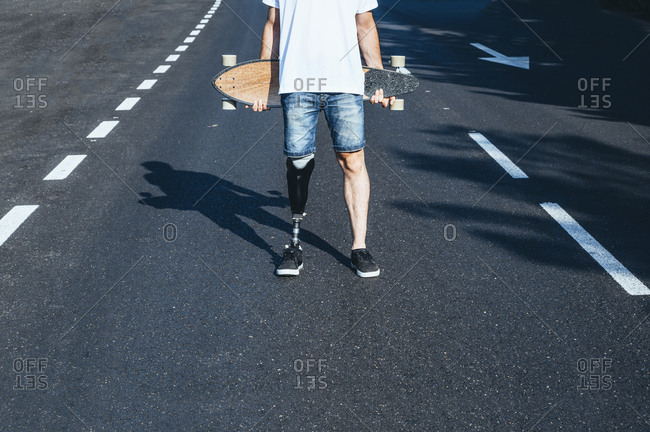 Young man with leg prosthesis holding skateboard on a road