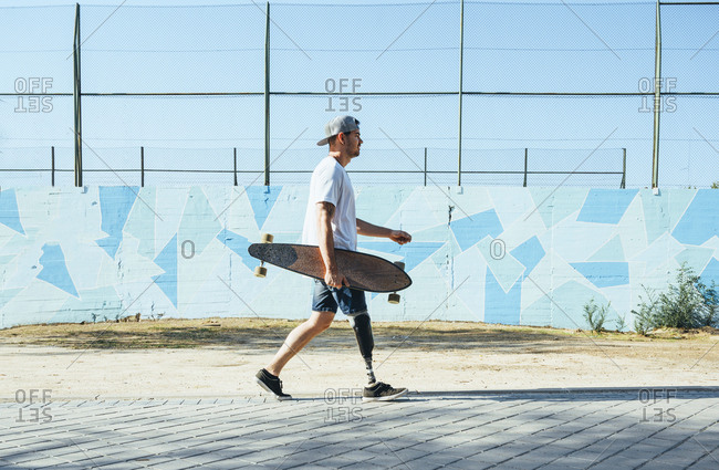 Young man with leg prosthesis walking and holding skateboard