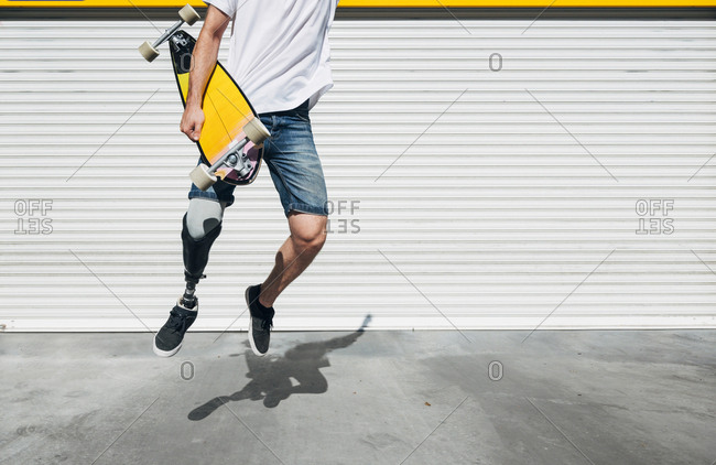 Young man with leg prosthesis holding skateboard and jumping