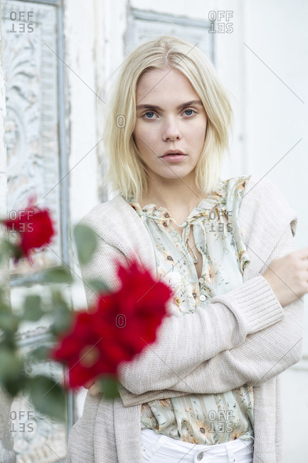 Portrait of blond young woman wearing summer blouse with floral design and cardigan