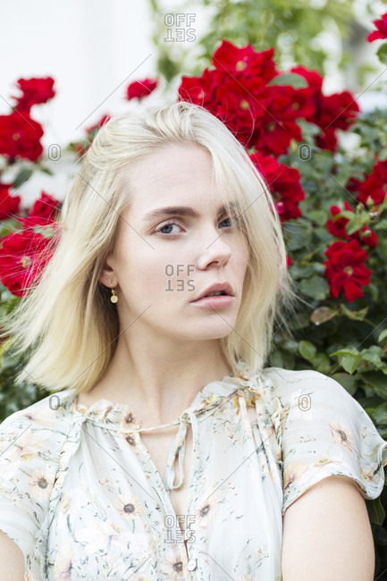 Portrait of blond young woman wearing summer blouse with floral design