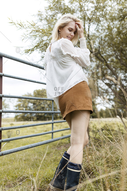 Portrait of blond young woman wearing white blouse- mini skirt and Wellington Boots