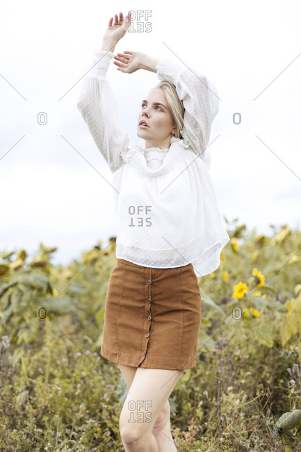 Portrait of blond young woman wearing white blouse dancing on sunflower field