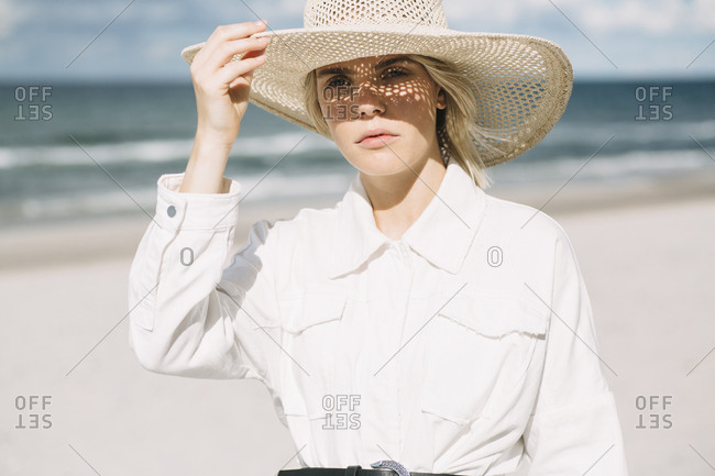 Portrait of blond young woman wearing white shirt and summer hat on the beach