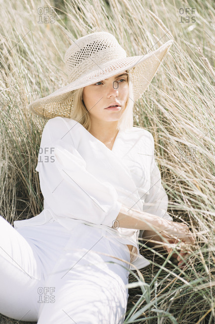 Portrait of blond young woman lying in beach dunes wearing white wrap blouse and summer hat