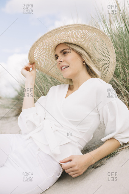 Portrait of blond young woman laying in beach dunes wearing white wrap blouse and summer hat
