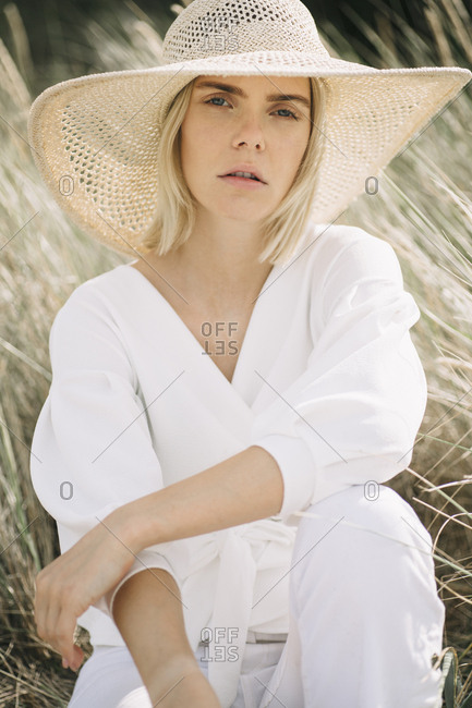 Portrait of blond young woman in dunes wearing white wrap blouse and summer hat