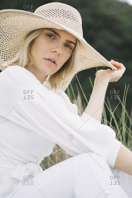 Portrait of blond young woman sitting in dunes wearing white wrap blouse and summer hat