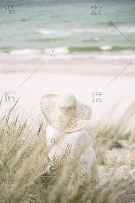 Back view of woman wearing summer hat sitting on the beach looking to the sea- Ruegen- Germany