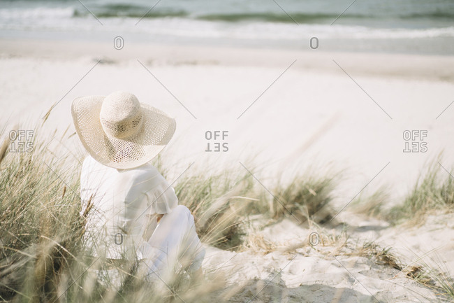 Back view of woman wearing summer hat sitting on the beach looking at the sea- Ruegen- Germany