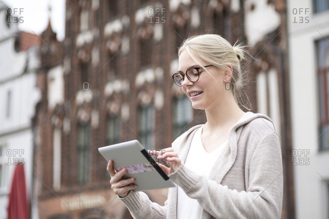 Portrait of young woman using tablet in the city