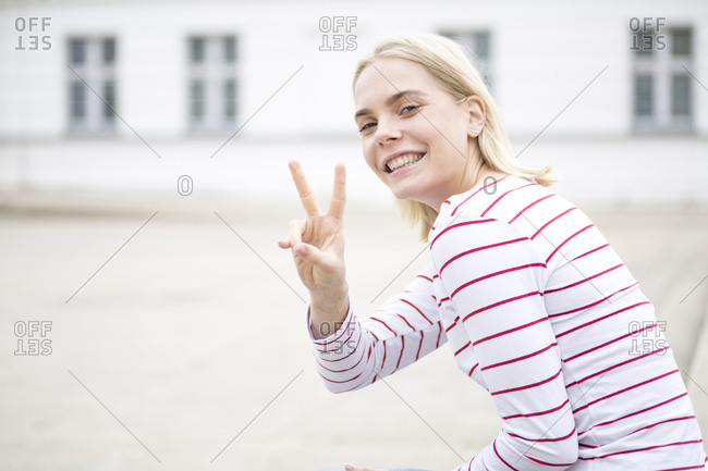 Portrait of young blond woman showing peace sign