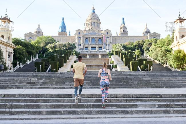 Man and woman running on stairs at Palau Nacional- Barcelona- Spain