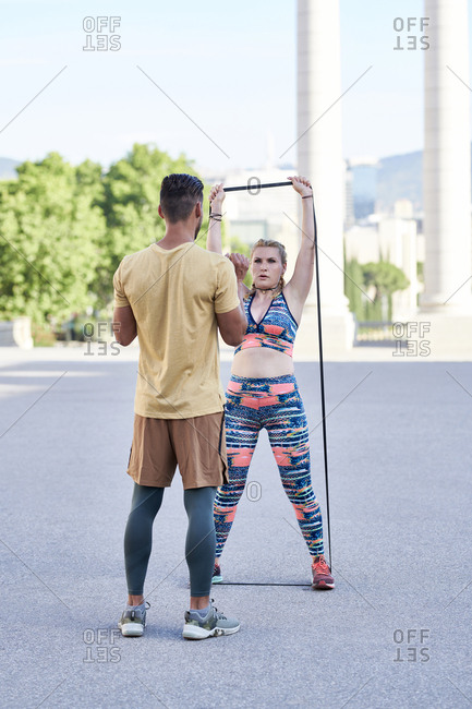 Fitness coach practicing with young woman outdoors in the city