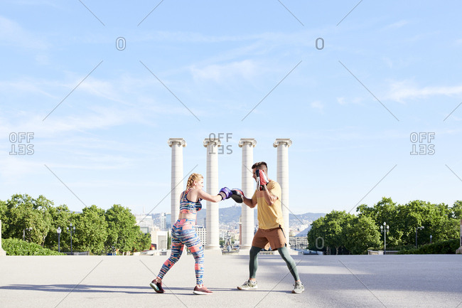 Fitness coach practicing boxing class with young woman outdoors in the city