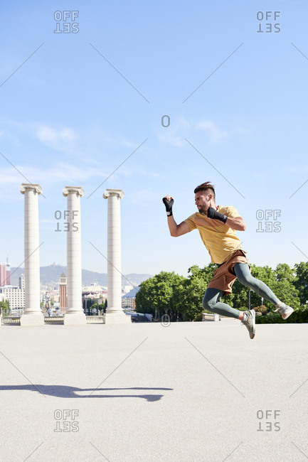 Man doing kickboxing exercise outdoors in the city