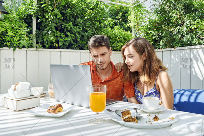 Young couple using laptop during breakfast