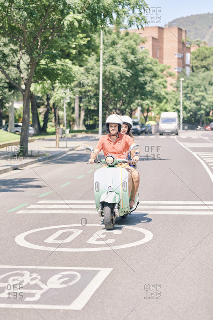 Young couple riding vintage motor scooter on urban road