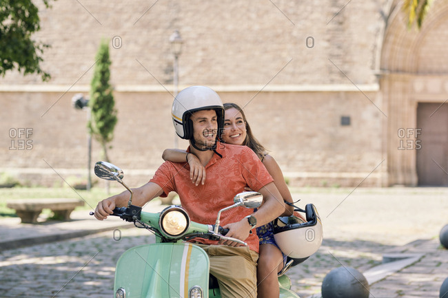 Young couple on a vintage motor scooter outdoors