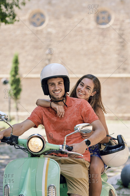 Portrait of a smiling young couple on a vintage motor scooter